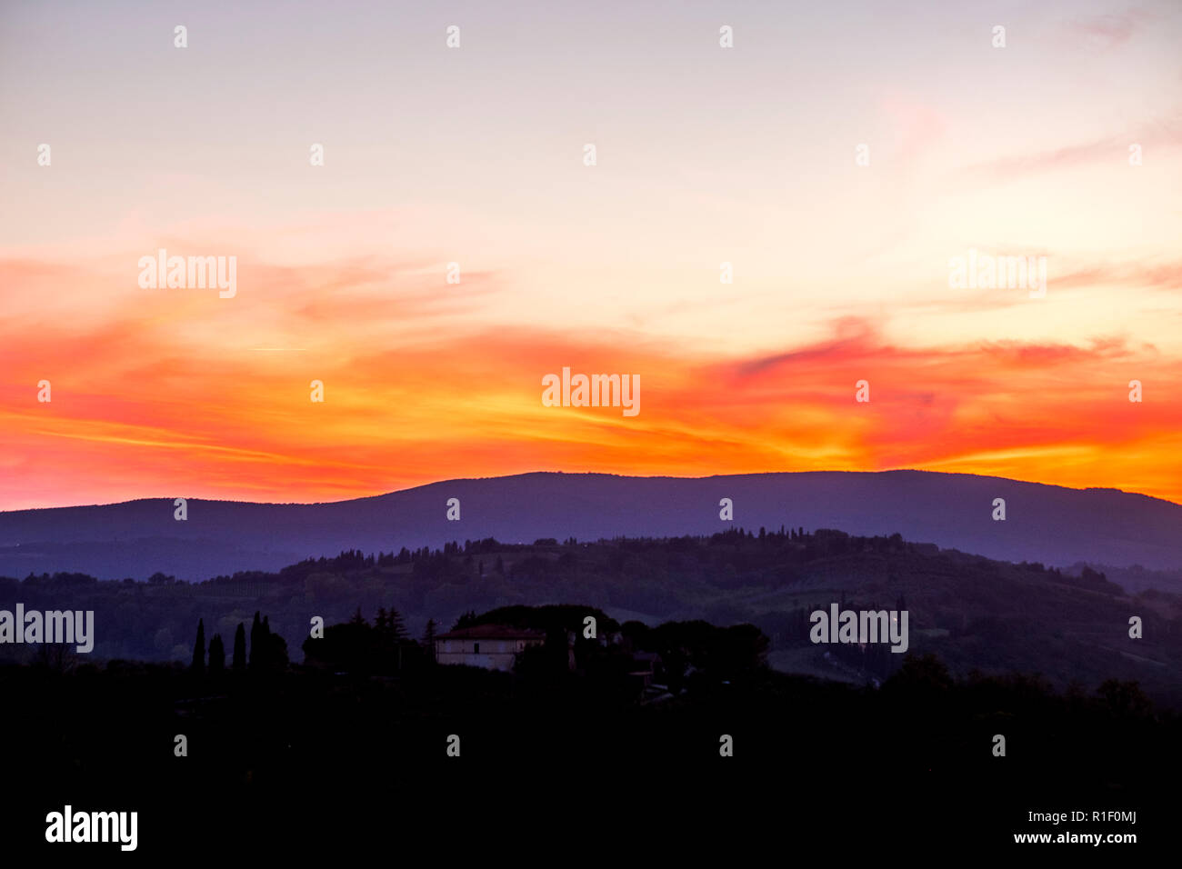Amazing coloured sunset in Tuscany Italy with red clouds and blue ground during the blue hours. Beautiful landscape with colors and feeling - Stock Image