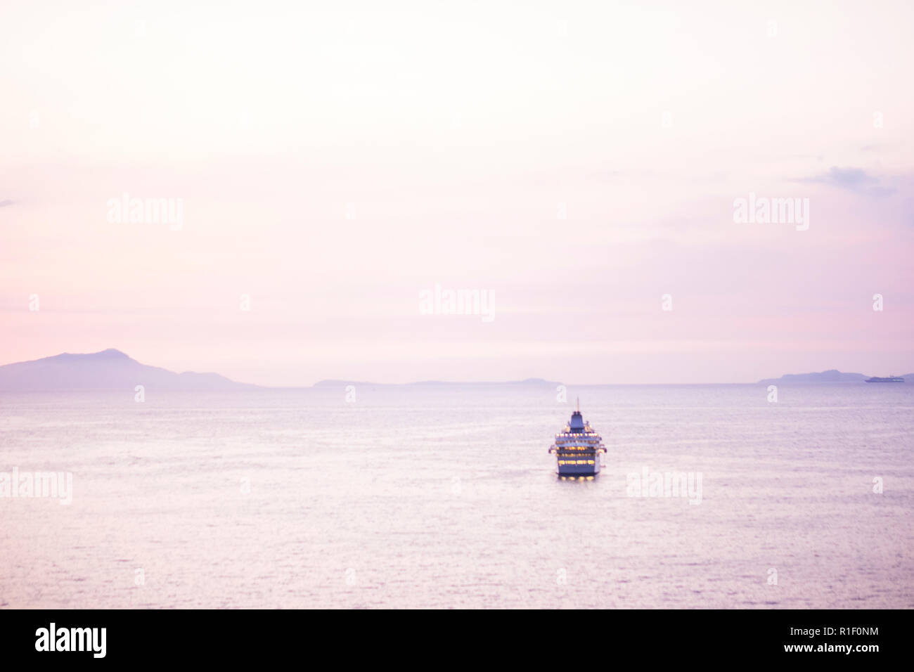 Touristic cruise boat in the middle of a quiet sea after the sunset with a pink coloured nice sky for all the people wander to travel and enjoy the va Stock Photo