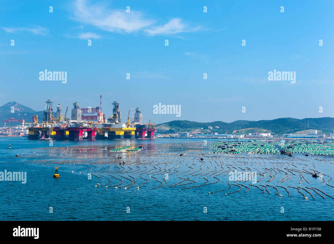 YANTAI, SHANDONG, CHINA - 21JUL2018: Semisubmersible rigs, owned by CIMC and subsidiaries compete for space with traditional fish farming. - Stock Image