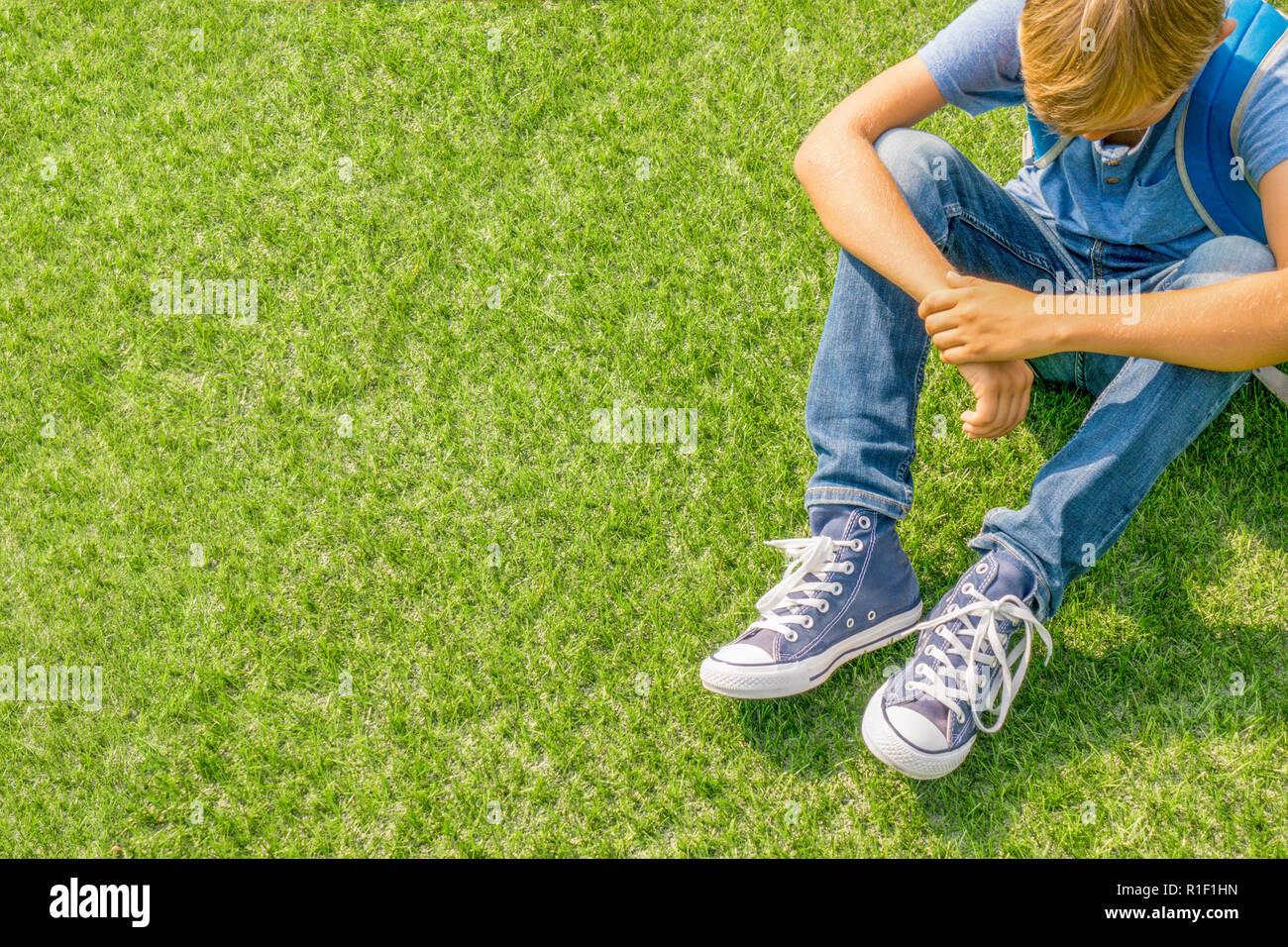Unhappy sad upset boy sitting alone on the grass. - Stock Image