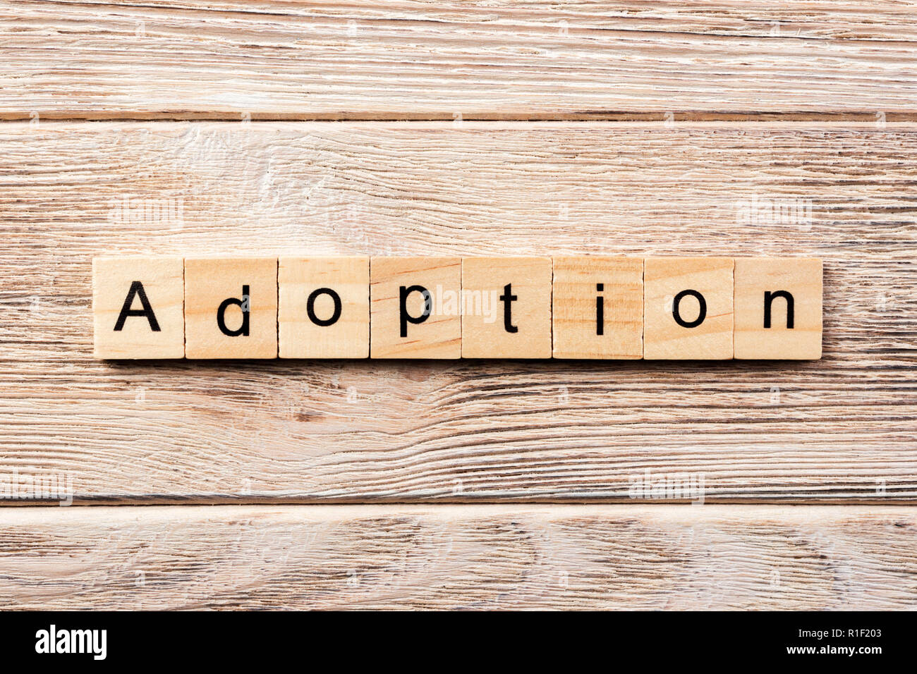 adoption word written on wood block. adoption text on table, concept. - Stock Image
