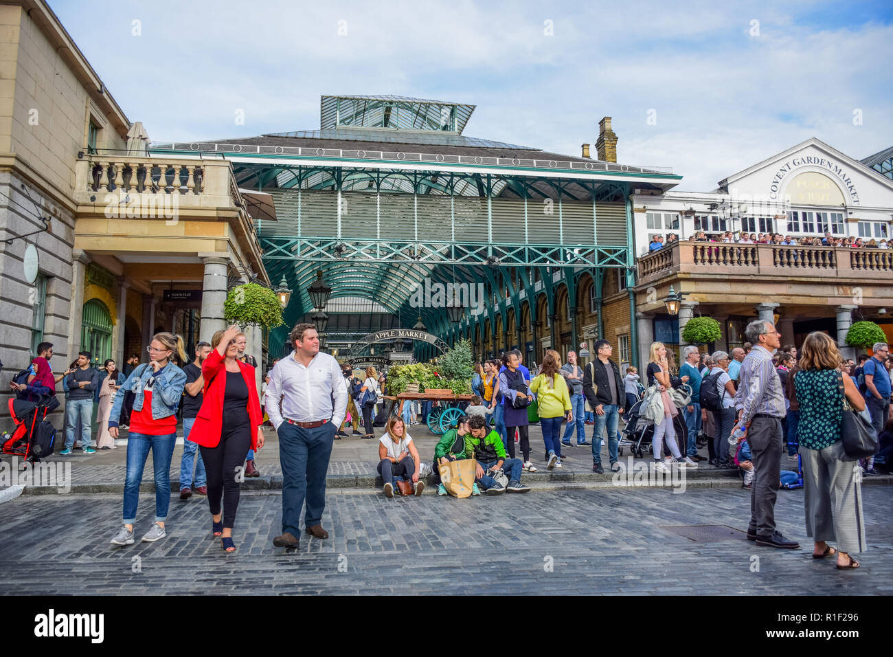Tourists spending their time at Covent Garden market, one of the most popular shopping and tourist sites in London, United Kingdom - Stock Image