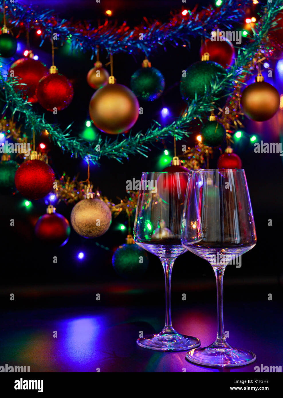 Colorful Christmas Lights Background.Two Wine Glasses Against A Background Of Colorful Christmas
