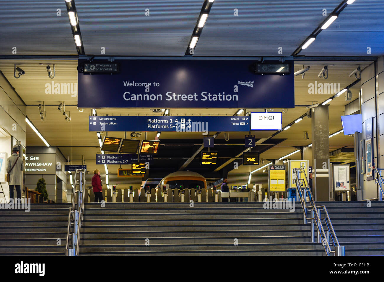 Cannon Street Station entrance with railway trains and very few passengers. Signs. Steps. Space for copy - Stock Image