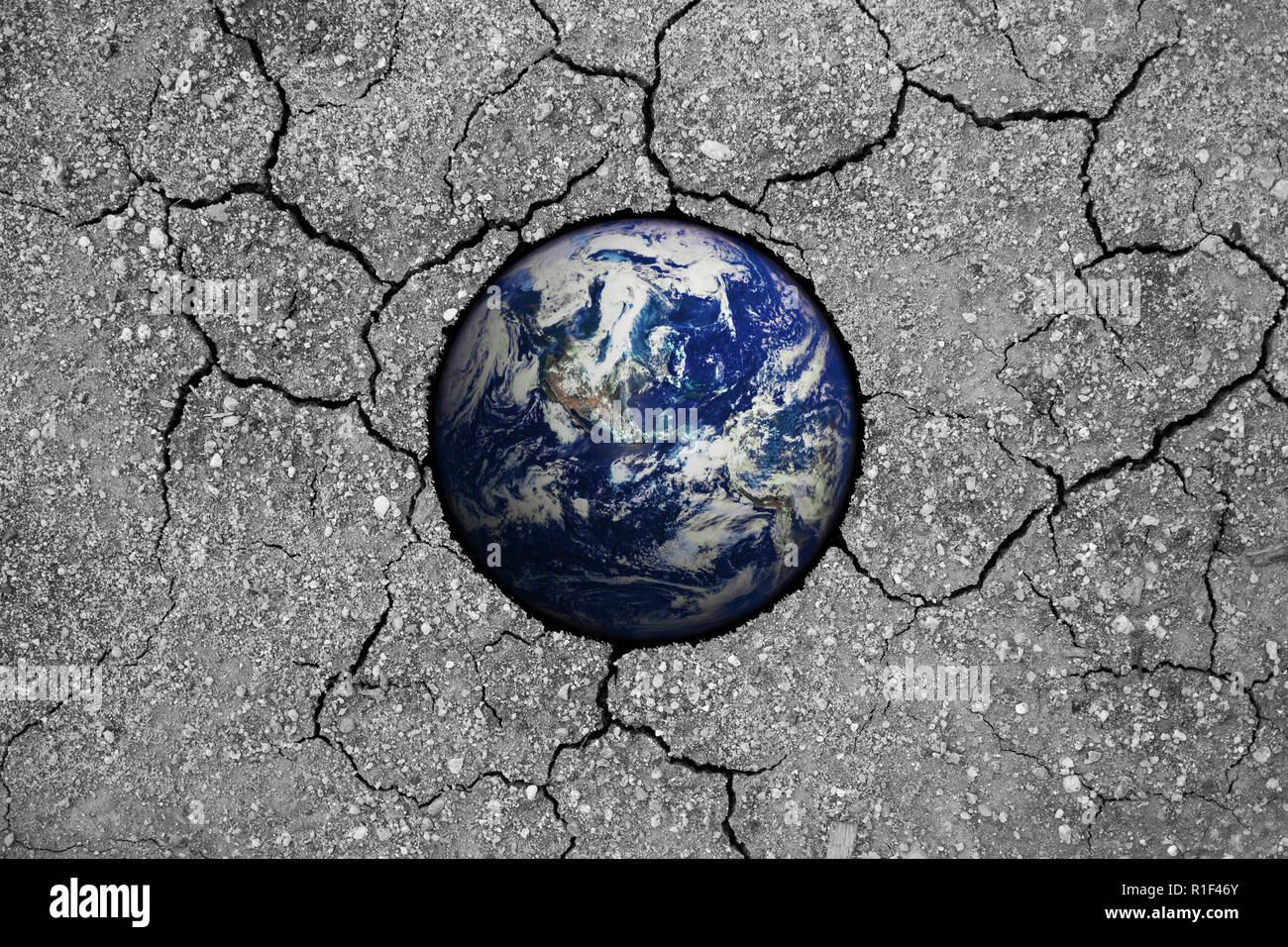 13e1687fb49 Dying planet earth half buried in dry cracked clay representing global  warming