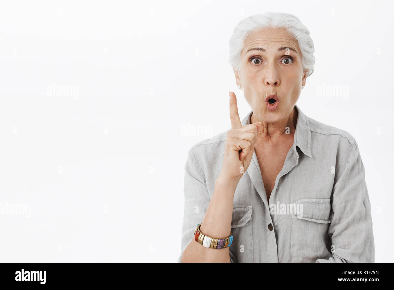 I got excellent advice for daughter. Portrait of excited and enthusiastic creative senior woman with white hair folding lips raising index finger in eureka gesture while having idea adding suggestion - Stock Image