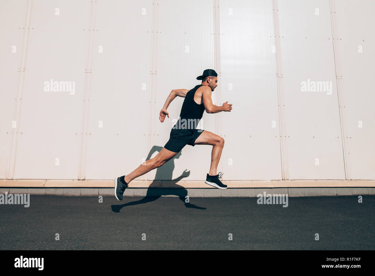 Runner man running fast in industrial city background. Sport, athletics, fitness, jogging activity - Stock Image