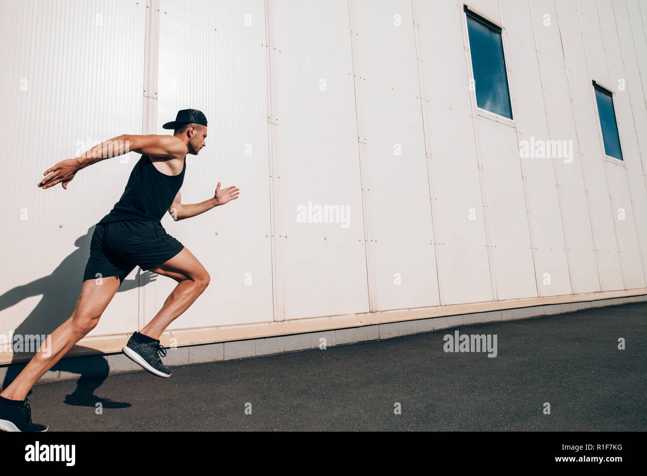 Sporty man runner running in city sreet. Sport, health, fitness, jogging - Stock Image