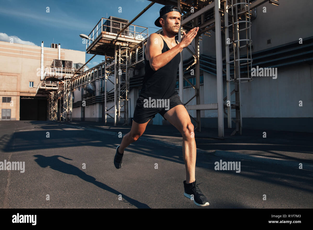 Sporty man running fast in industrial city background. Sport, athletics, fitness, jogging activity - Stock Image