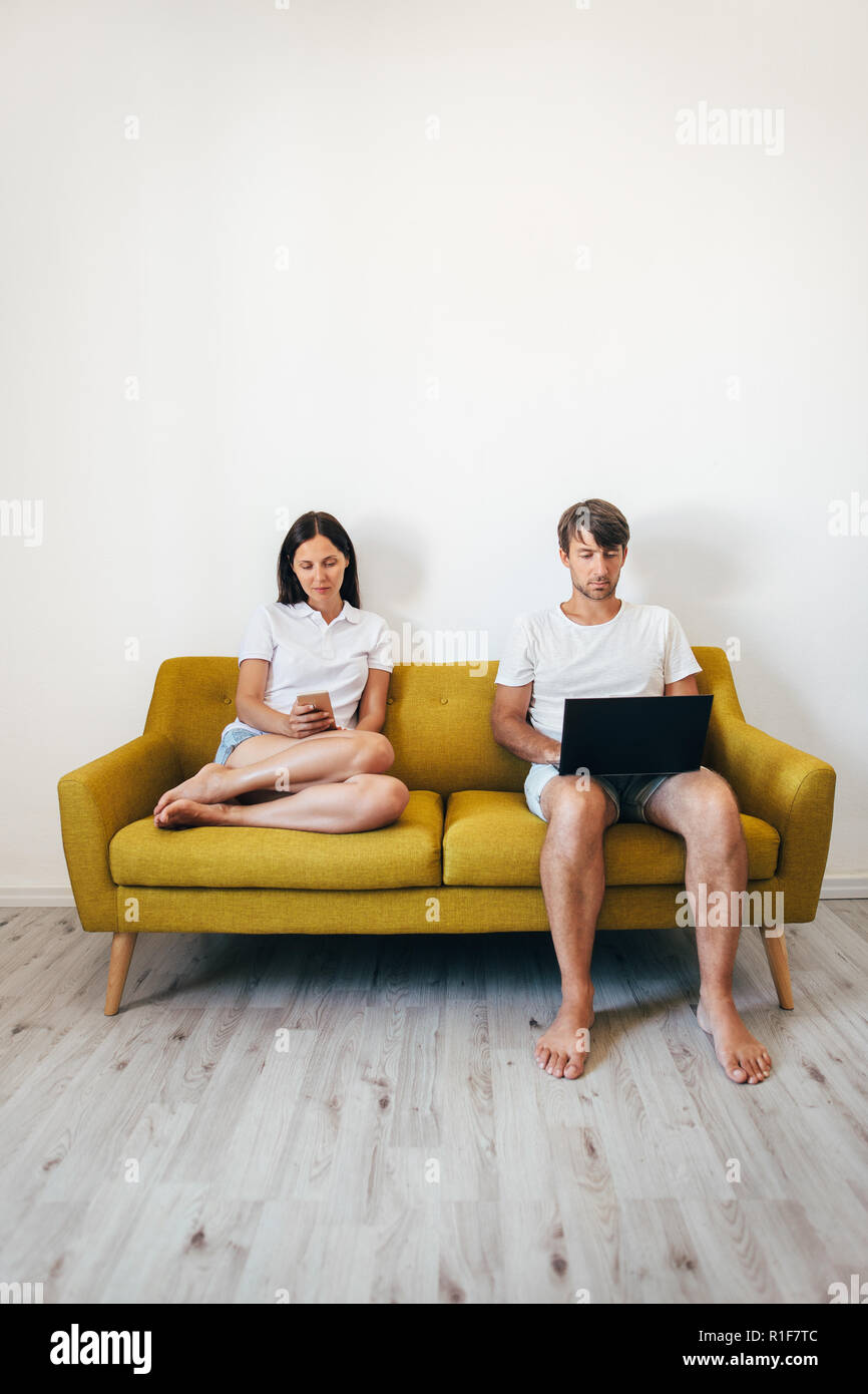 Young couple using gadgets while relaxing together at home - Stock Image