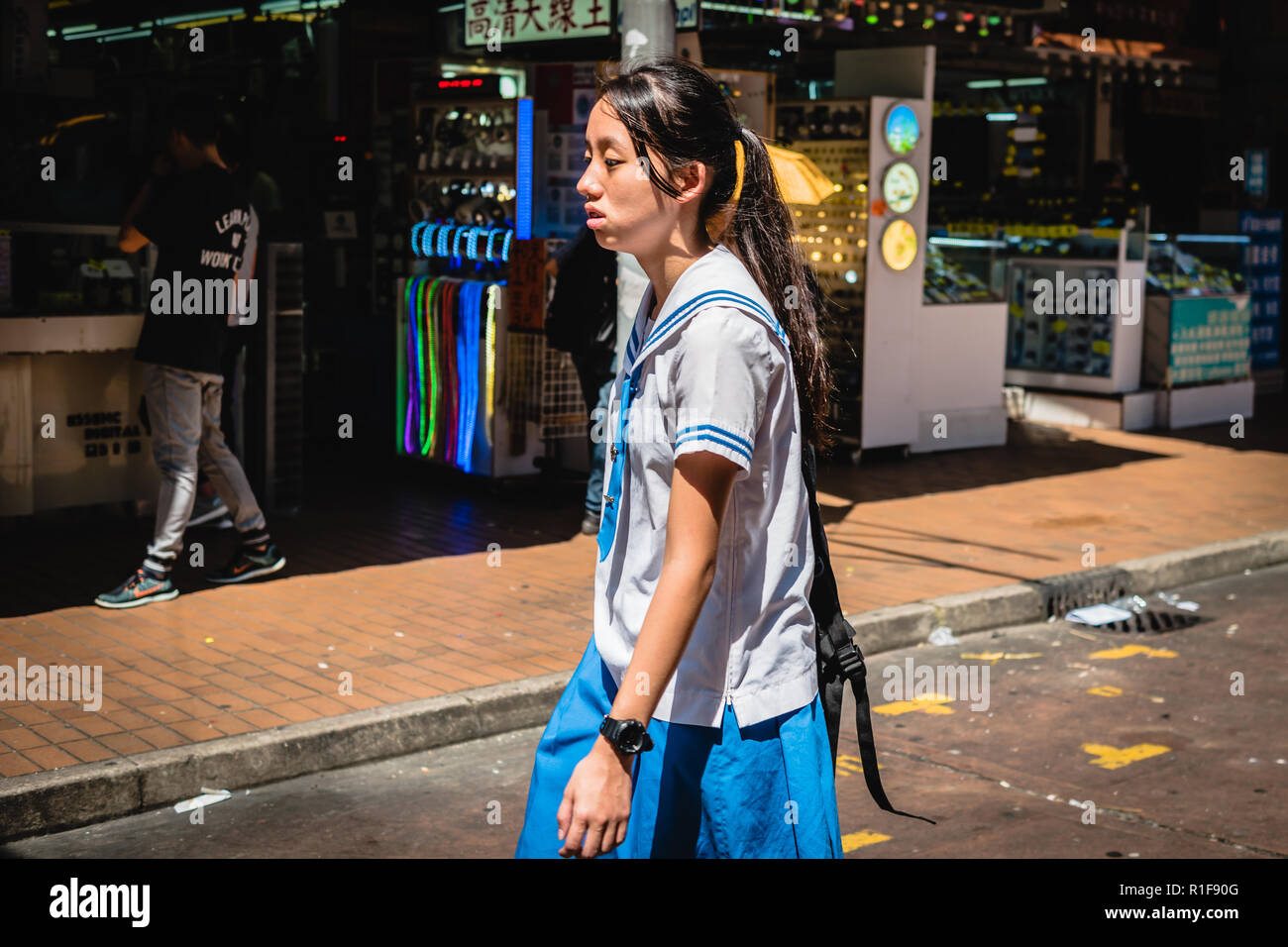 An exhausted schoolgirl is walking home in Hong Kong during a heat wave. - Stock Image
