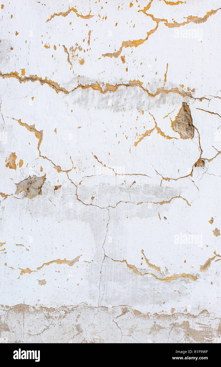 White scratched plaster wall background. Old wall with holes in plaster. Rough cracked stucco surface texture. Vertical photo - Stock Image