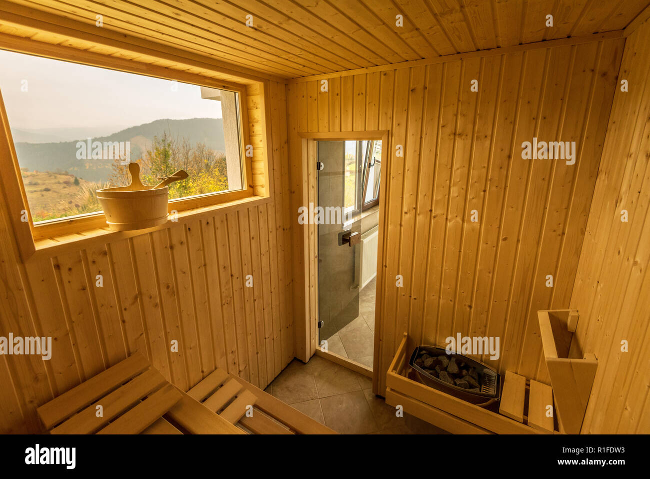 Wooden sauna with seats. Accessories interior of sauna spa. - Stock Image