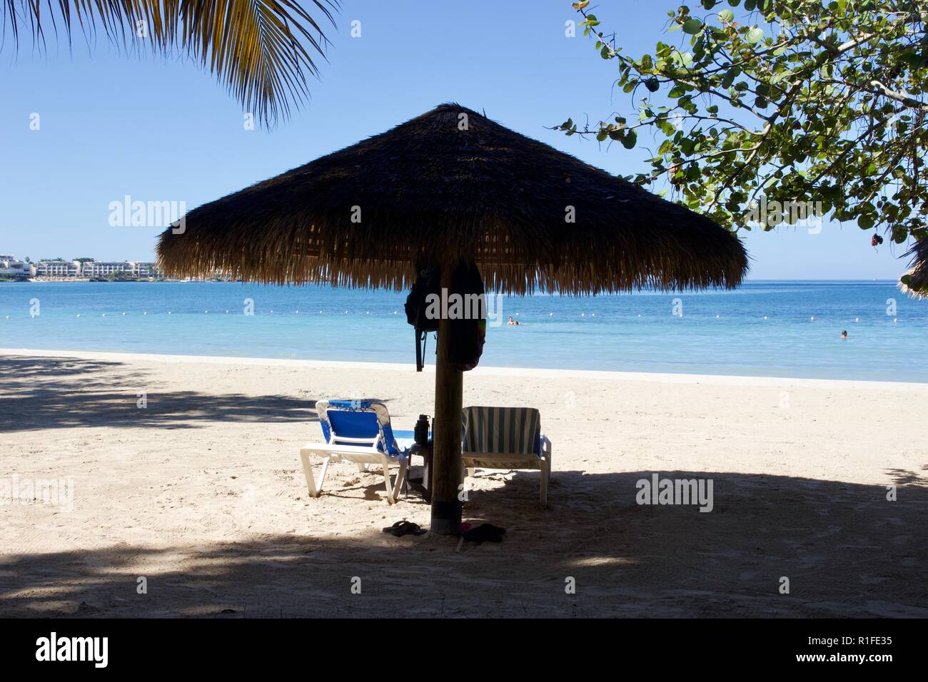 Beach shade provided by a thatched straw umbrella - Stock Image