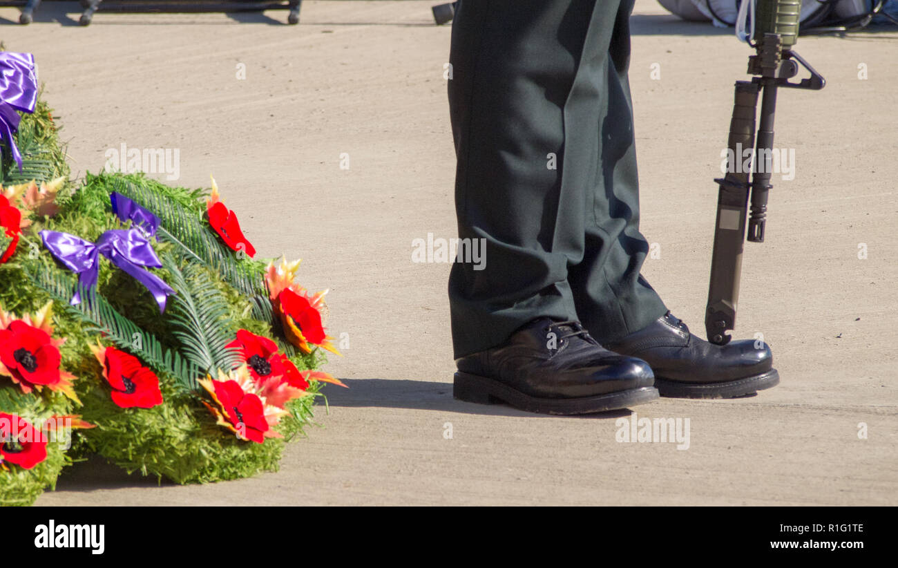 Wreath with poppies at the foot of an honour guard on remembrance day in Canada. - Stock Image