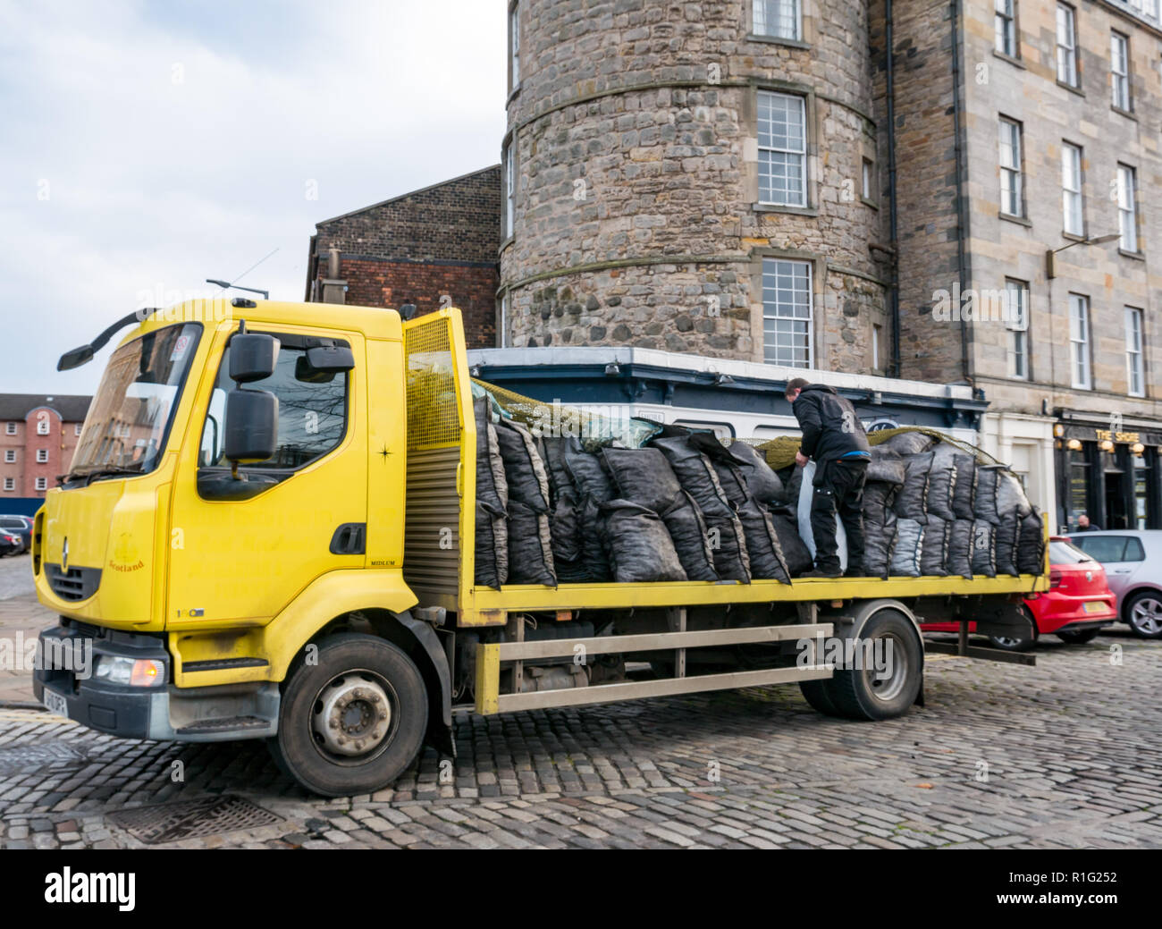 Flatbed lorry with man delivering coal sacks, Tower Place, Leith, Edinburgh, Scotland, UK - Stock Image