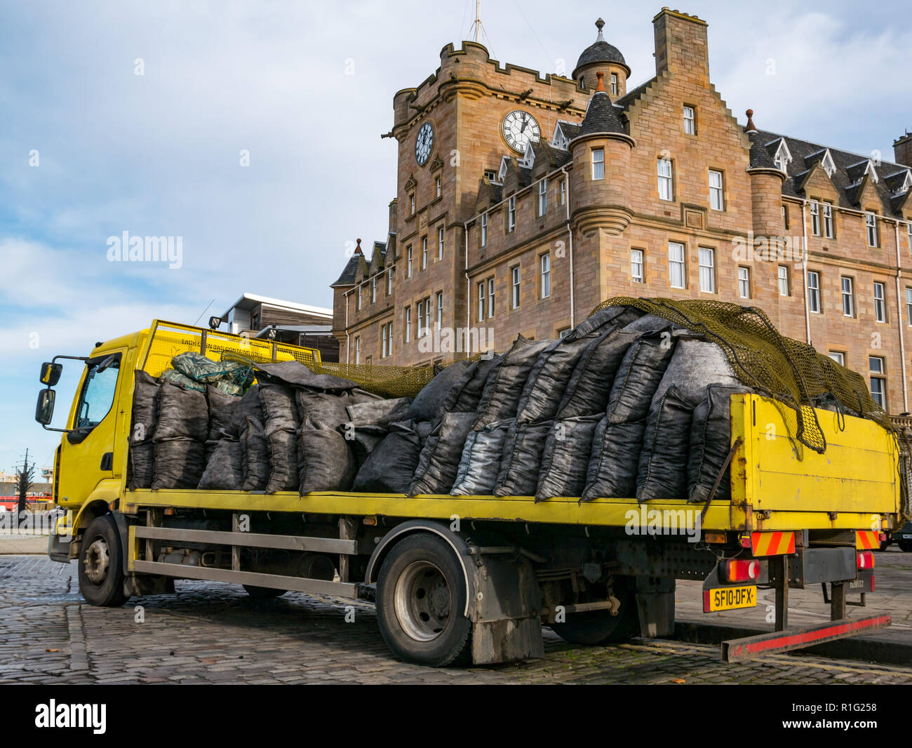 Yellow flatbed  lorry delivering coal sacks with Malmaison Hotel, Tower Place, Leith, Edinburgh, Scotland, UK - Stock Image