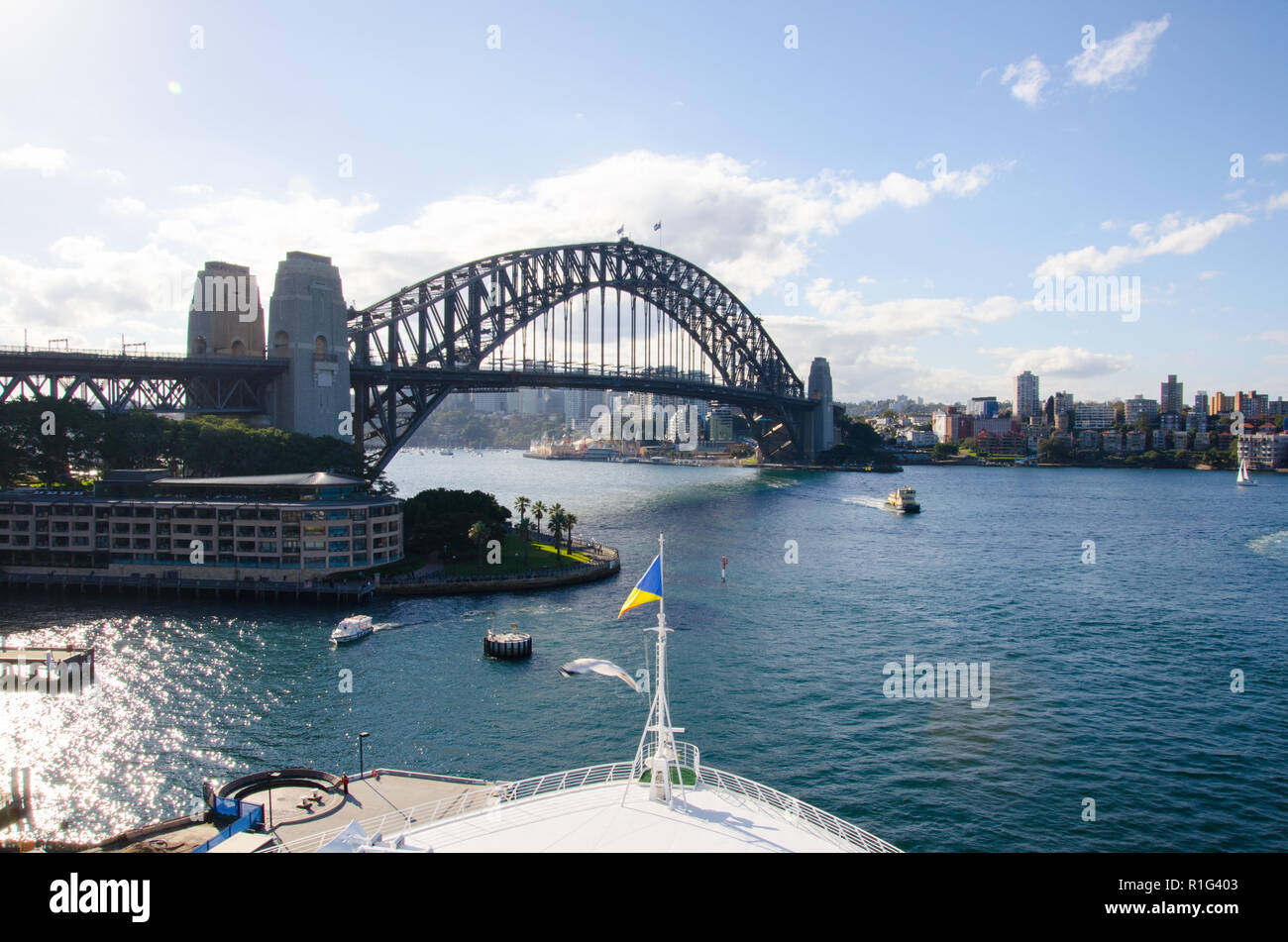 Looking across Sydney Harbour towards Sydney Harbour Bridge from deck of cruise ship docked at the Overseas Passenger Terminal in Circular Quay. - Stock Image
