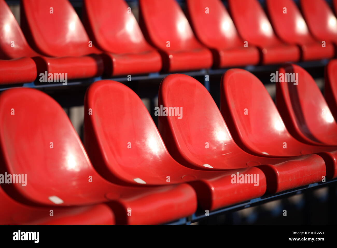 Red chairs bleachers in stadium close to - Stock Image