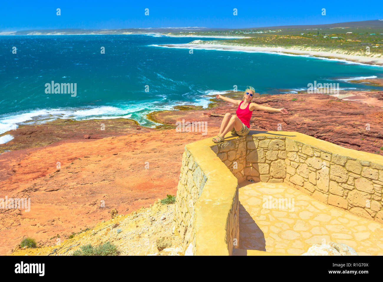 Carefree woman at Red Bluff in Kalbarri National Park. Pederick Lookout overlooking Red Bluff Beach in Australian Coral Coast on Indian Ocean. Sunny with blue sky. Western Australia coastal lookout. - Stock Image
