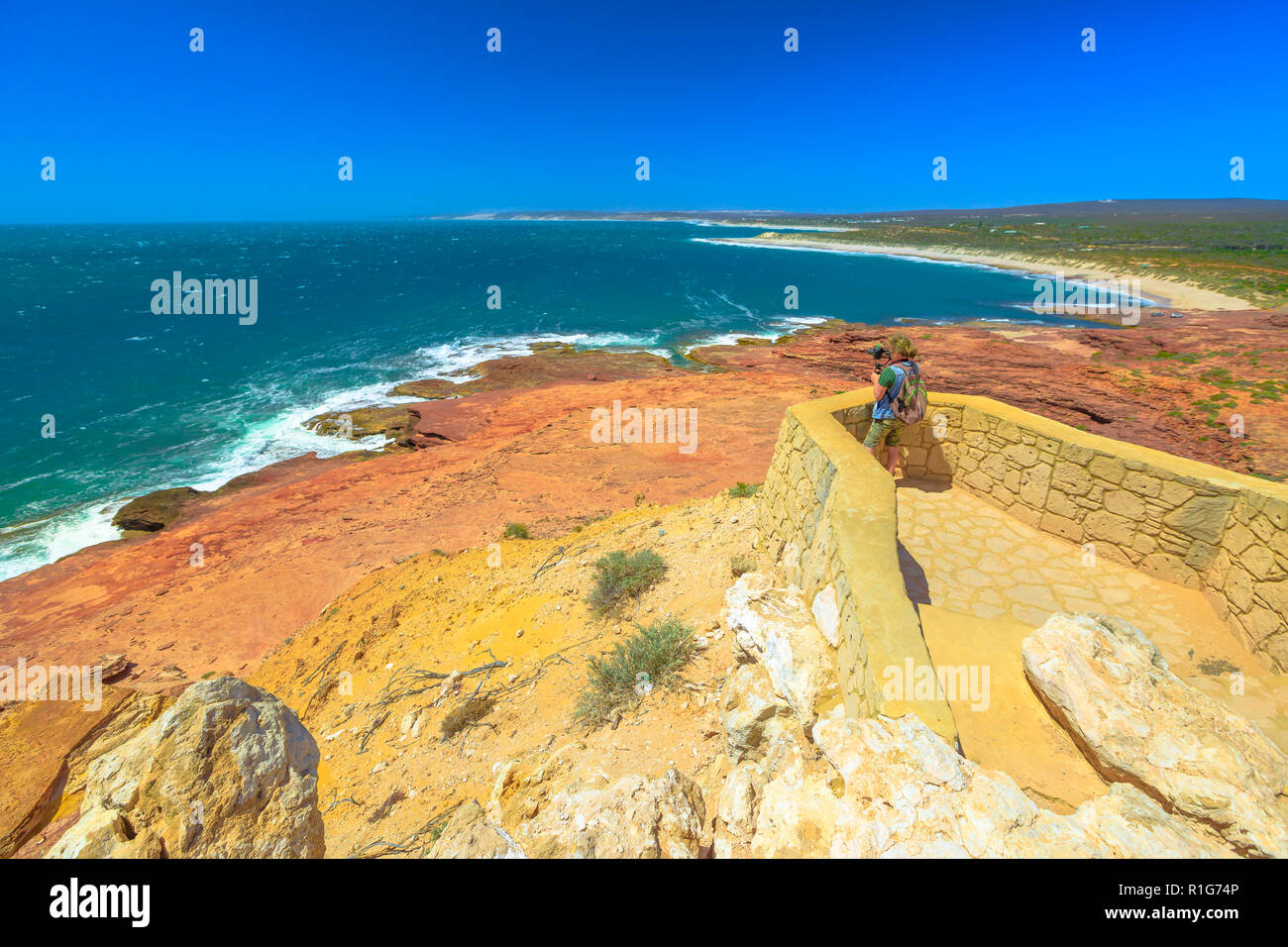 Travel photographer with stabilizer takes shot at Red Bluff lookout, Kalbarri National Park, Western Australia. Professional videomaker takes photo of Australian Coral Coast on Indian Ocean.Copy space - Stock Image