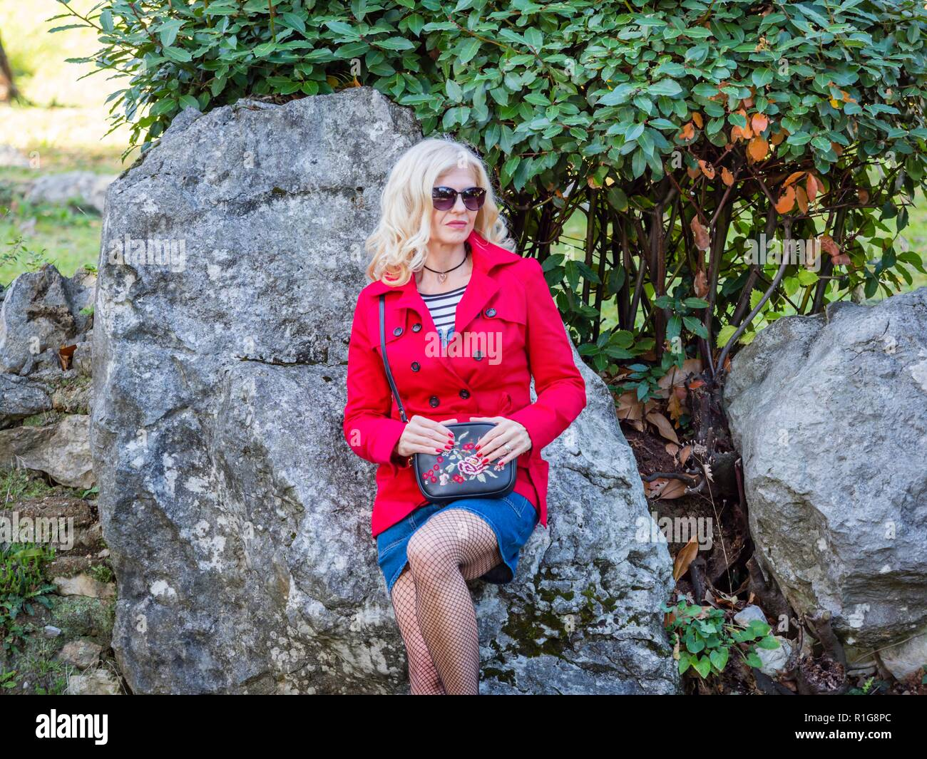 Attractive senior woman 40-45 years caucasian appearance blonde hair wearing sunglasses looking at camera - Stock Image
