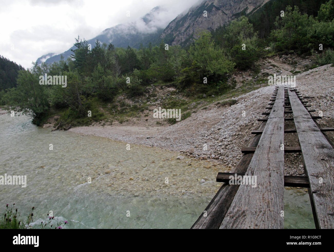 Wooden bridge across a mountain river in the Alps - Stock Image
