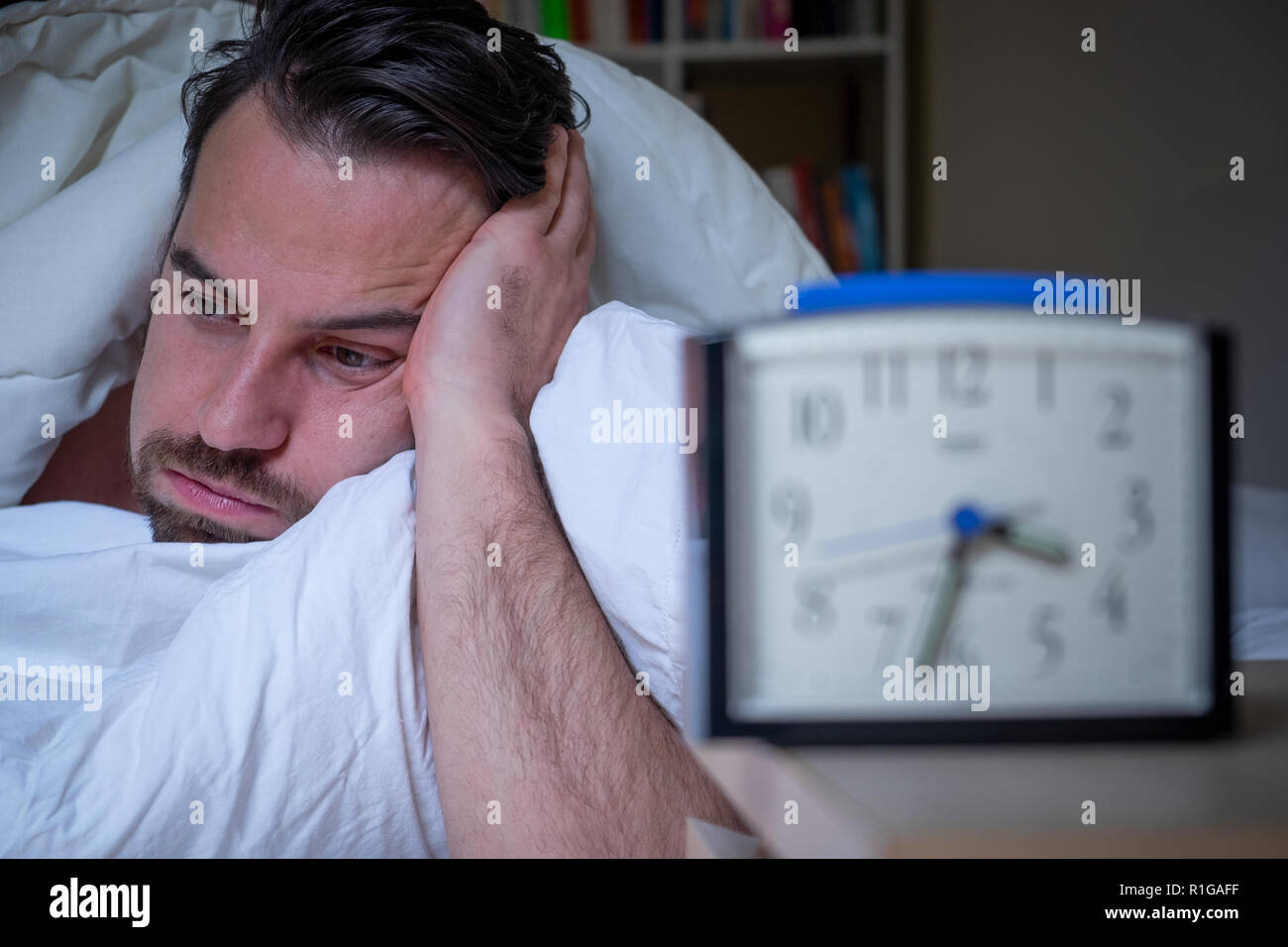 Anxious man suffering insomnia watching alarm clock - Stock Image