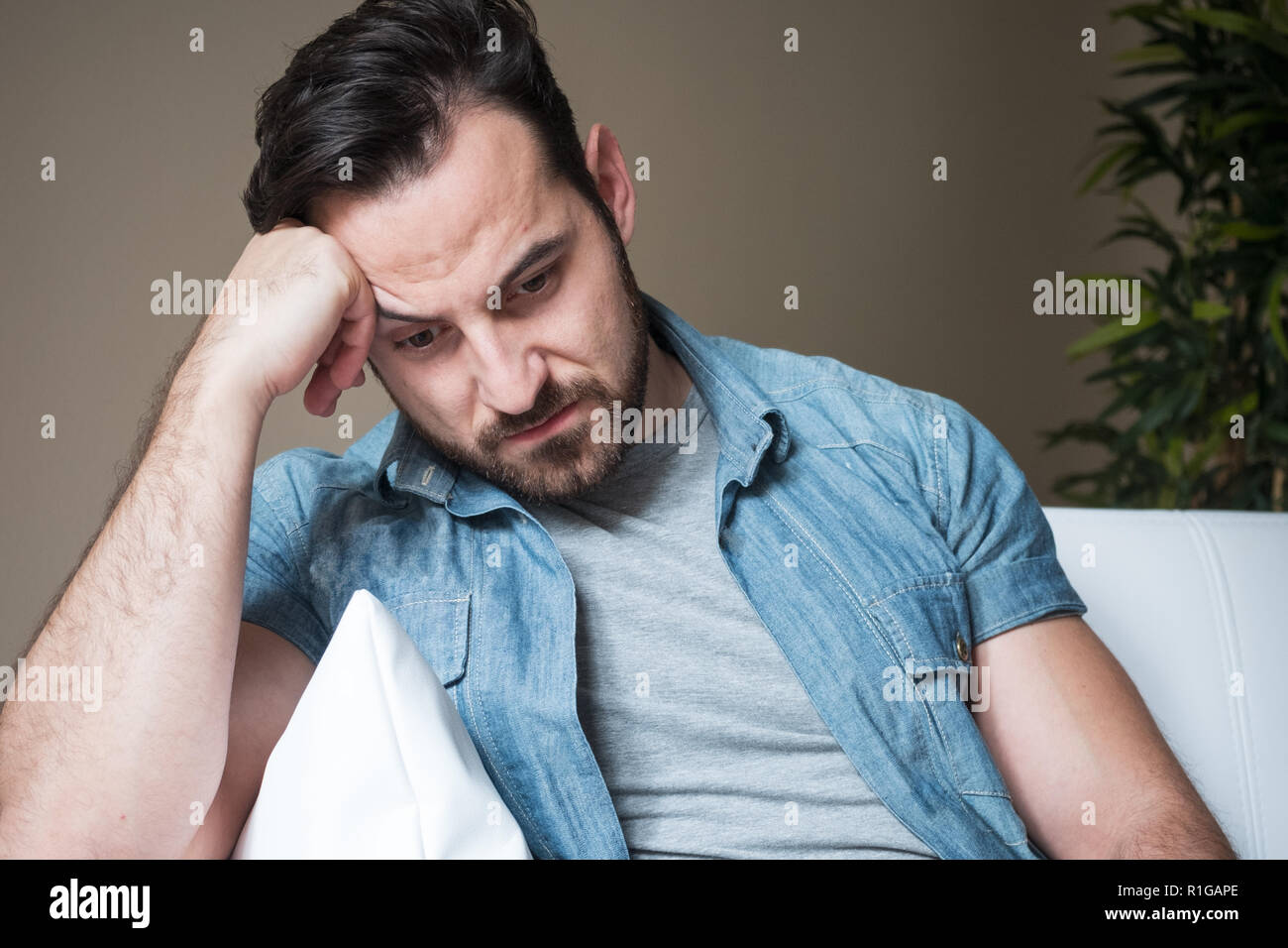 Man suffering and feeling alone at home sitting on the sofa - Stock Image
