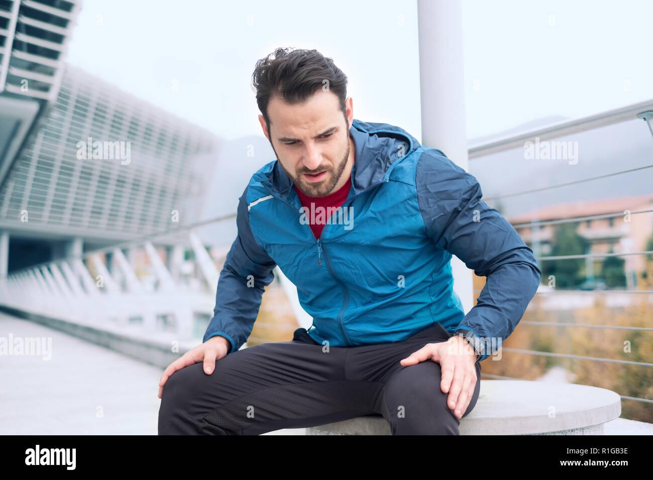 Active man resting during urban running training - Stock Image