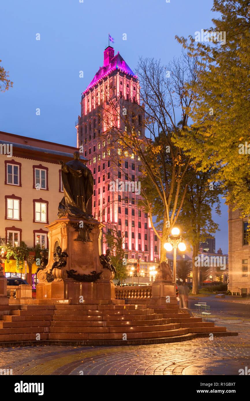Édifice Price (The Price Building) and Monument Cardinal-Taschereau at Place de l'Hôtel de Ville at dusk in Old Québec City, Québec, Canada. - Stock Image