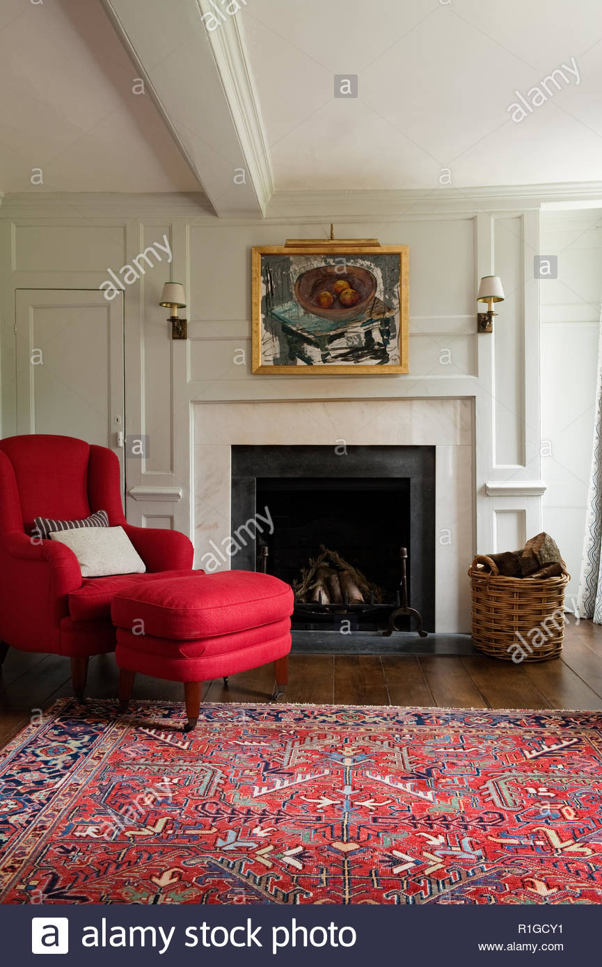 Red armchair by fireplace - Stock Image