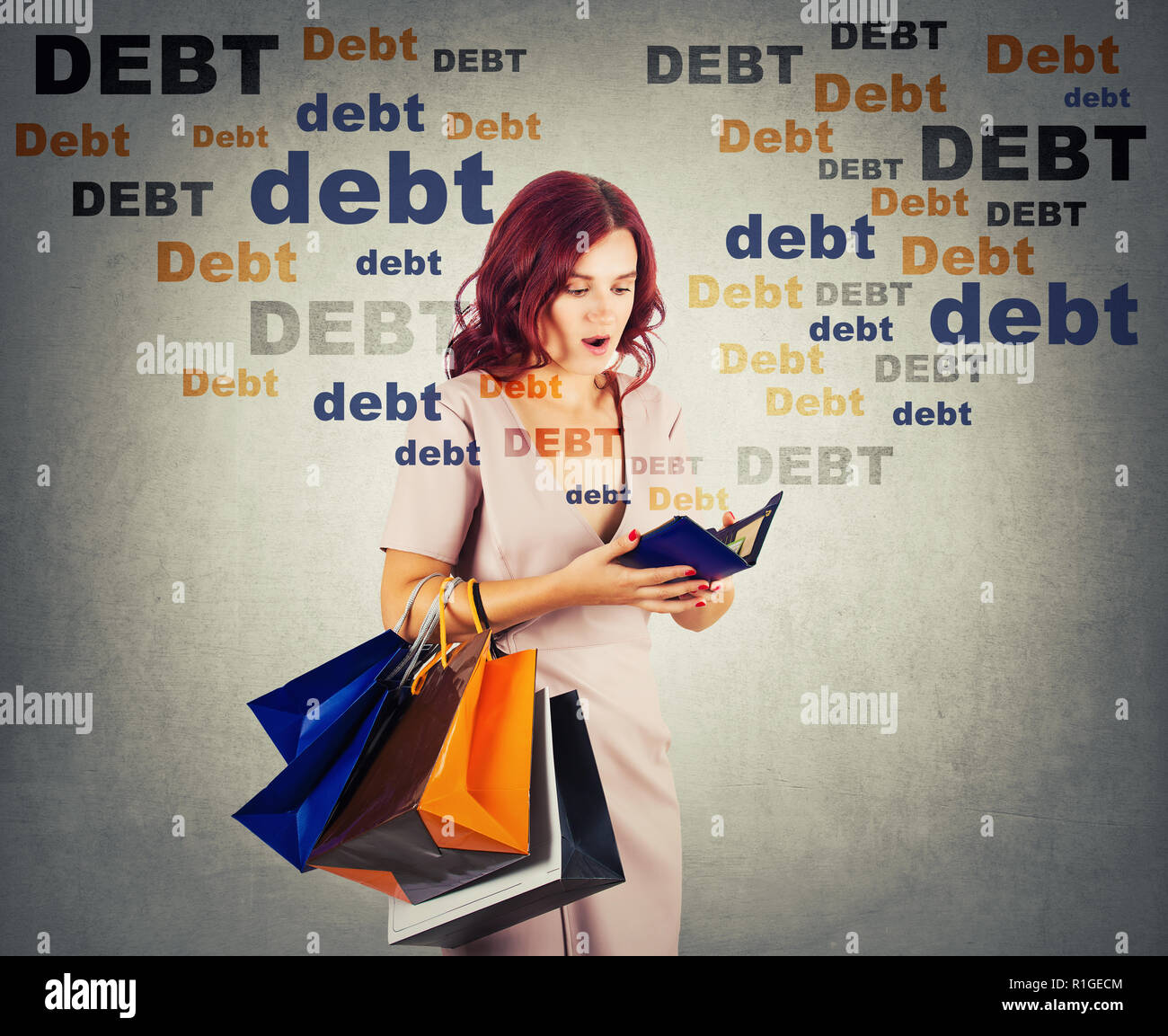 Young woman shopaholic carrying bags holding a empty wallet, shocked about huge debt amount, has no money for shopping in her pouch. Overspending conc - Stock Image