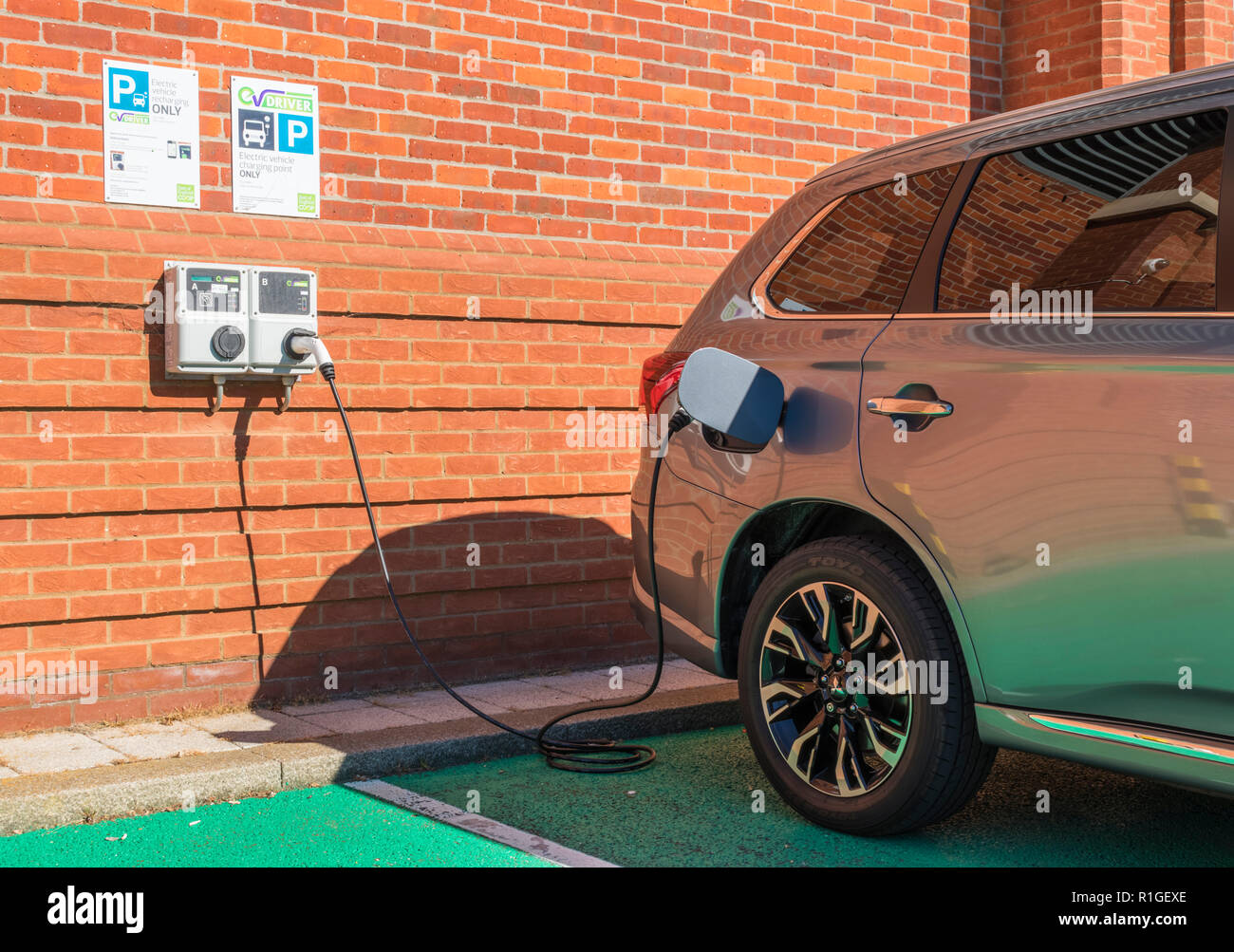 Mitsubishi outlander PHEV plugged in and charging at an EV Driver EV electric car charging point hybrid car charging Aldeburgh Suffolk England UK Stock Photo