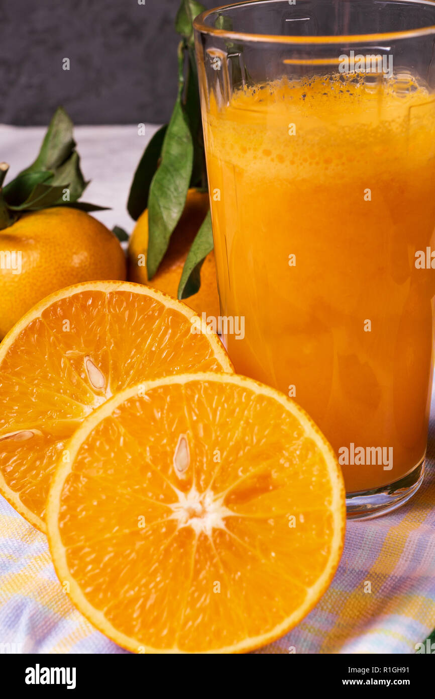 Flat lay view of Orange juice in a glass and ripe orange fruit, on blue and white napkin, over rustic background. - Stock Image