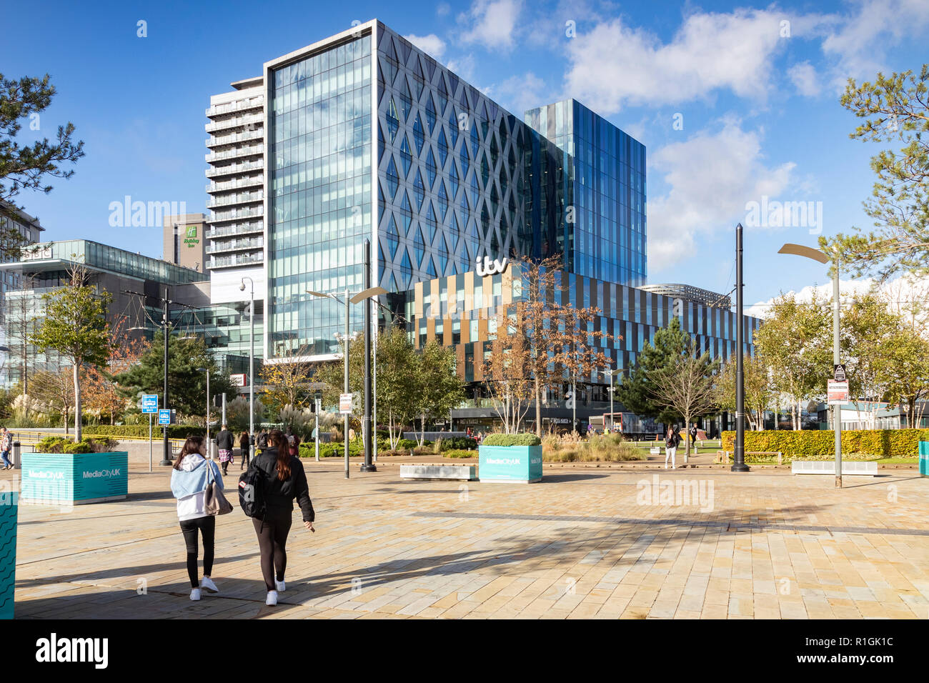 2 November 2018: Salford Quays, Manchester, UK - ITV buildings on a sunny autumn day, clear blue sky, two young women walking towards building. - Stock Image