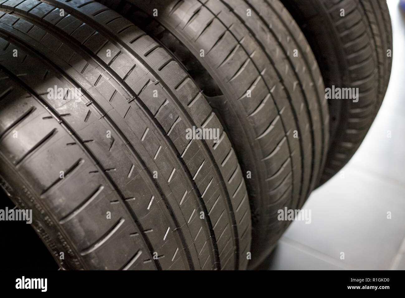 Tires for sale at a tire store and Stacks of old used tires and new one.all season car tires.Selective focus.Car service. all season car tires Stock Photo