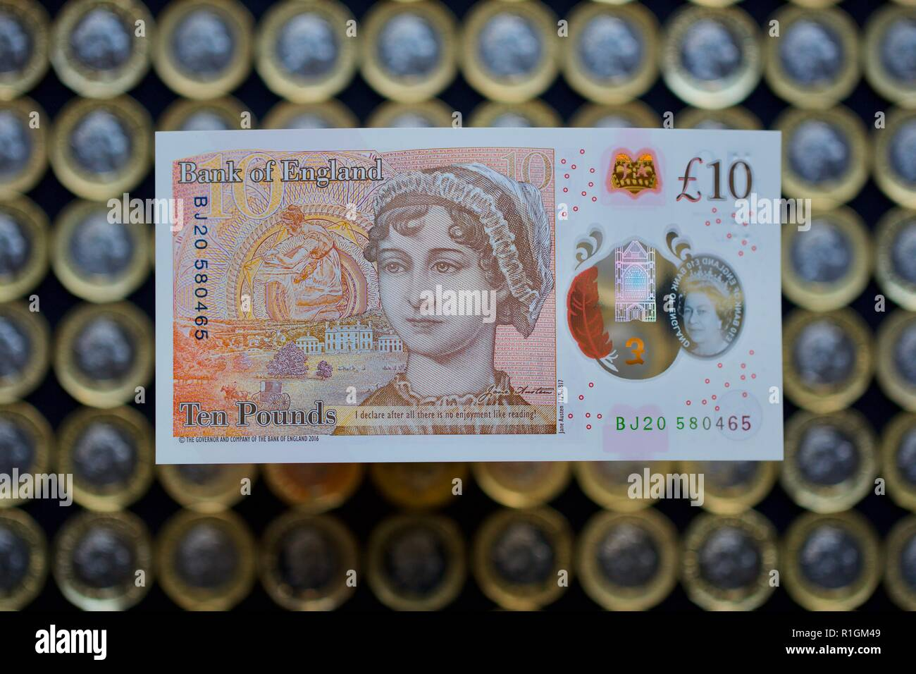 The new polymer £10 note, featuring Jane Austen, with the new £1 coins in the background - Stock Image