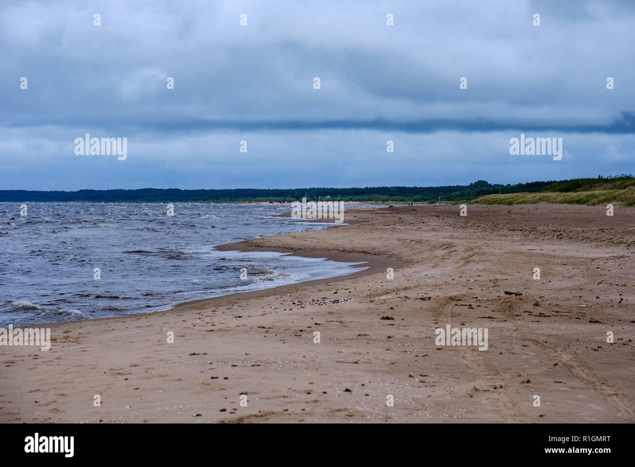 dirty beach by the sea with storm clouds above in calm evening - Stock Image
