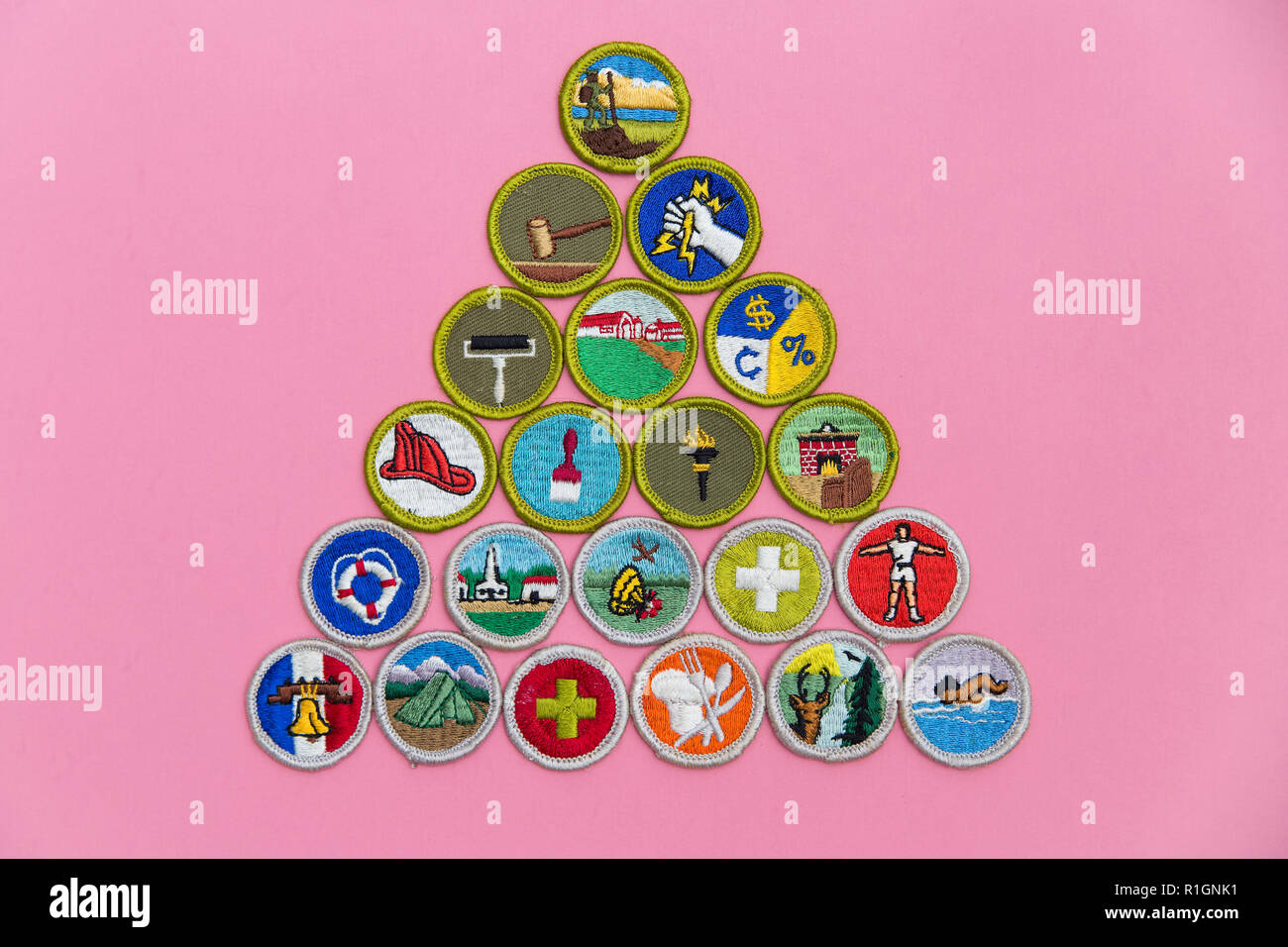 SAINT LOUIS, UNITED STATES - AUG 22, 2018:  A geometric arrangement of Boy Scouts of America (BSA) merit badges on pink background as BSA welcomes gir - Stock Image