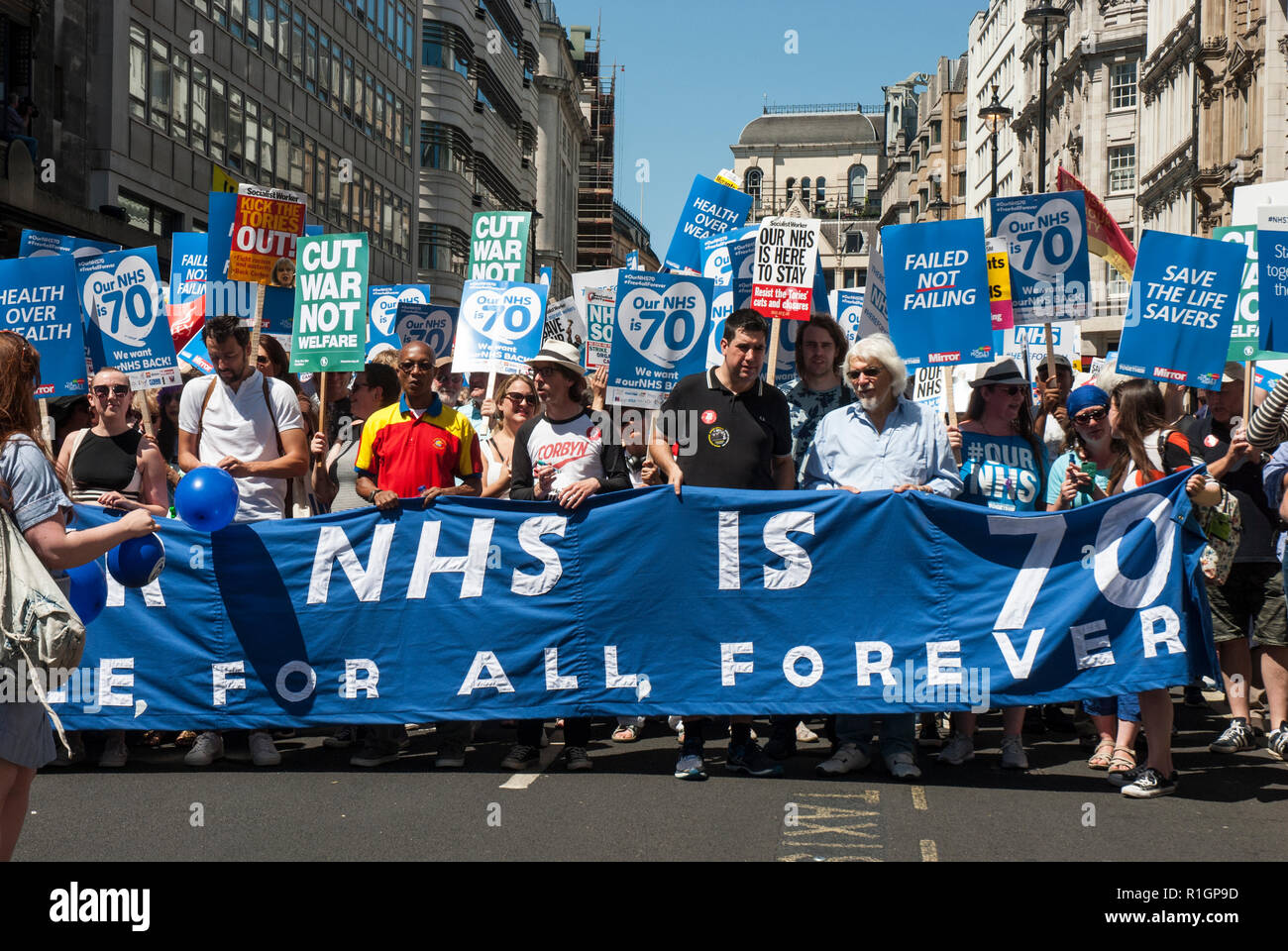70th anniversary rally to celebrate the founding of the NHS and protest against cuts with large leading banner and many placards, - Stock Image