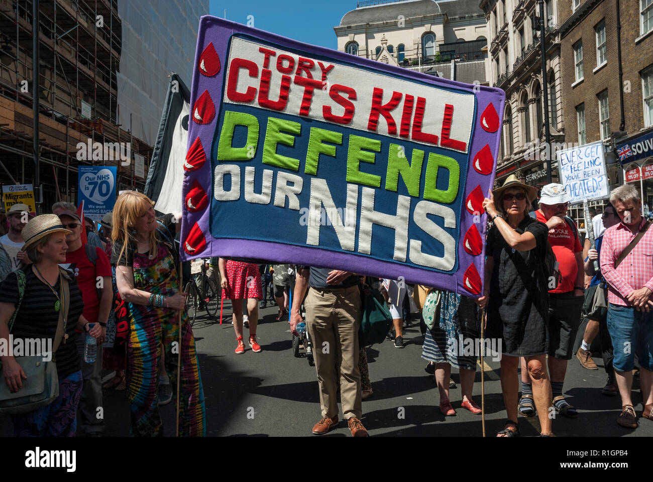 70th anniversary rally to celebrate the founding of the NHS and protest against cuts with a colourful banner 'Tory cuts kill/ defend our NHS' - Stock Image