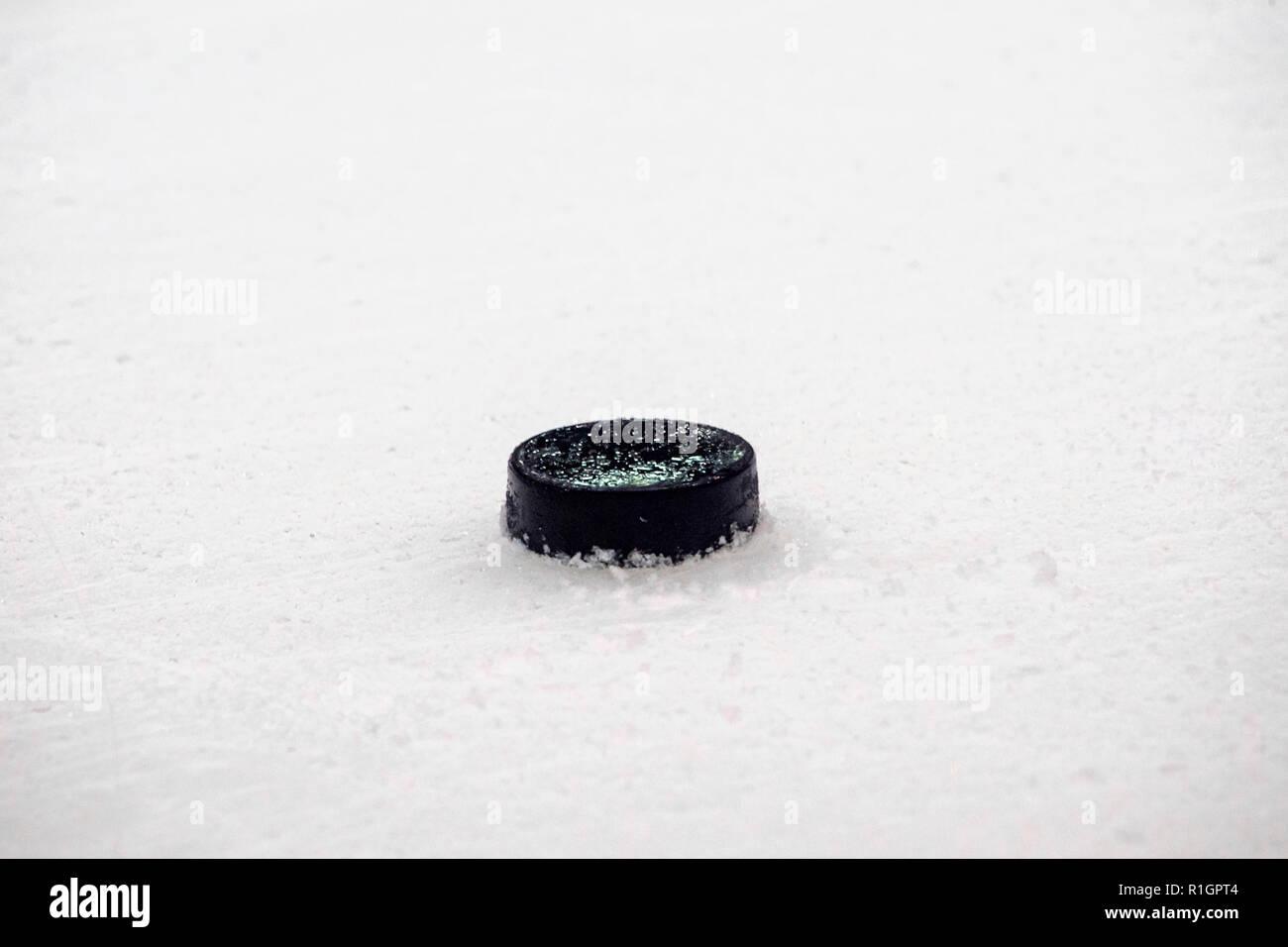 black hockey puck on ice rink. Winter sport. - Stock Image