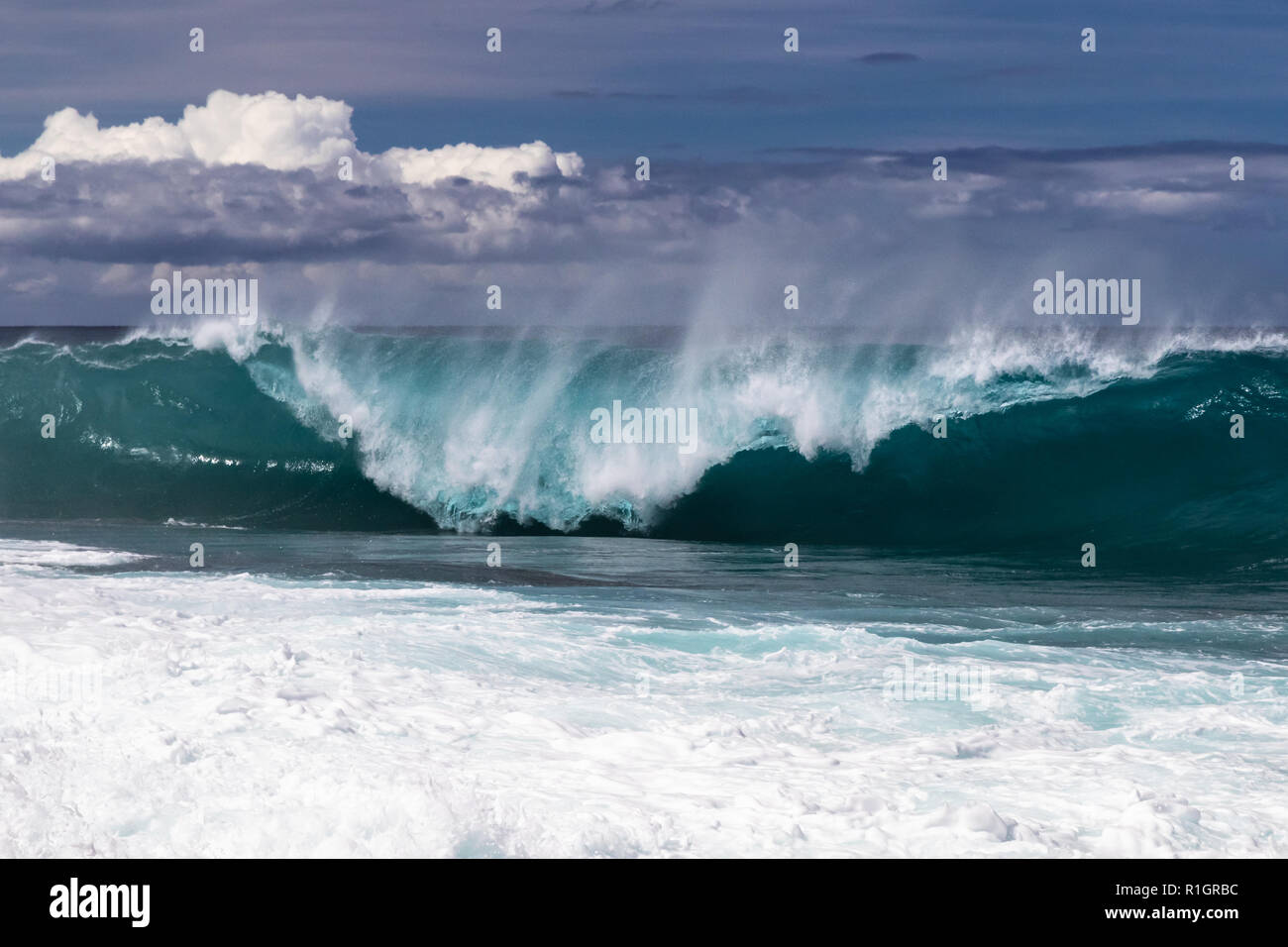 Wave curling on Hawaiian beach, about to crash on the water below. Spray flyng back on wave's top. South Point. White sea spray thrown into the air. Stock Photo