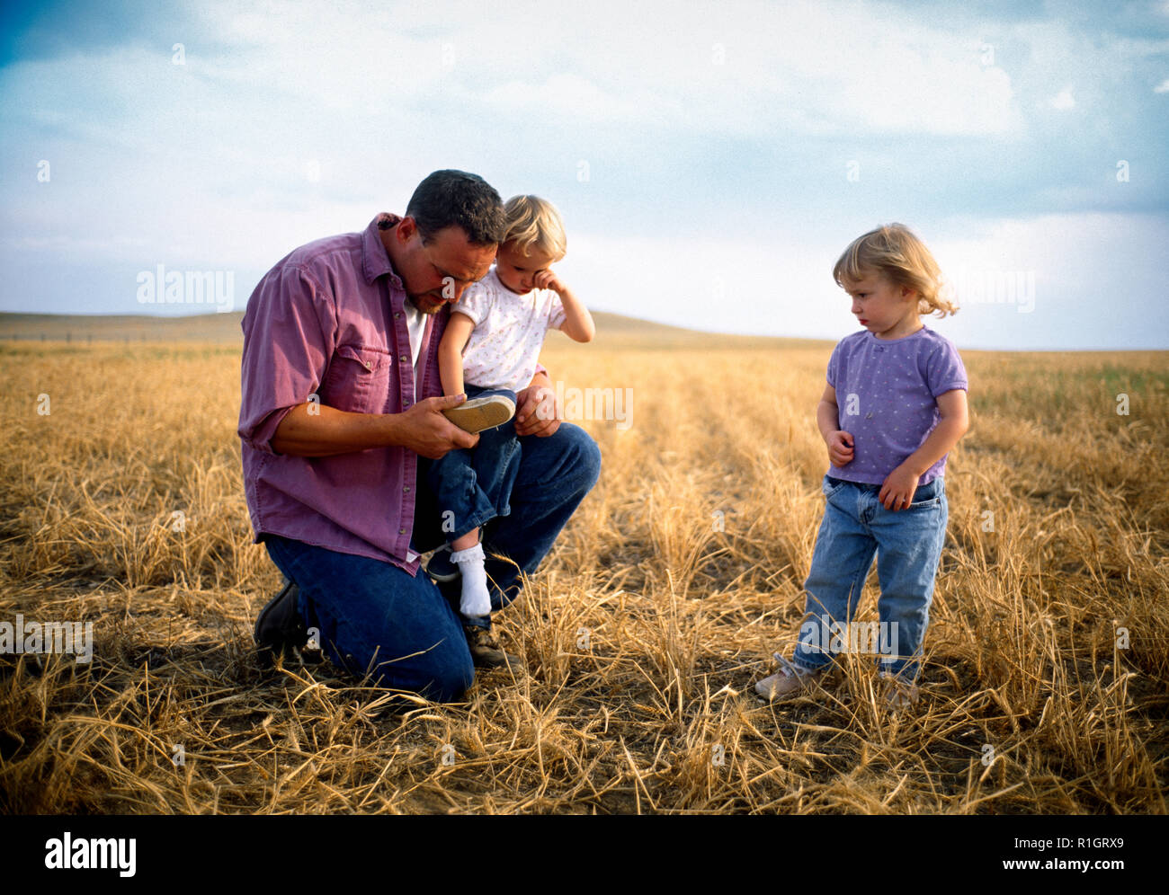Man crouching in a field with his young daughters - Stock Image