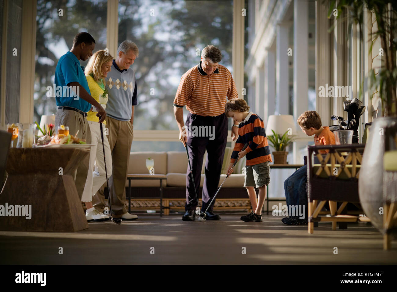 Young boy getting golf tips from his mid-adult father as his mother and two men watch. - Stock Image