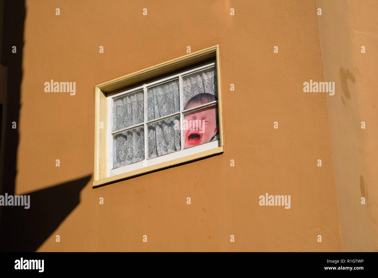 Image of a crying baby on a second story window in San Francisco, California, USA; street view, exterior. - Stock Image