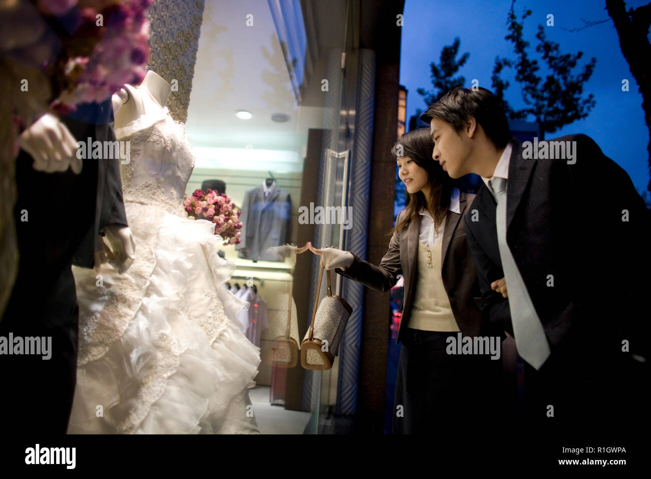 Young adult couple looking at a wedding dress through a shop window at twilight. - Stock Image