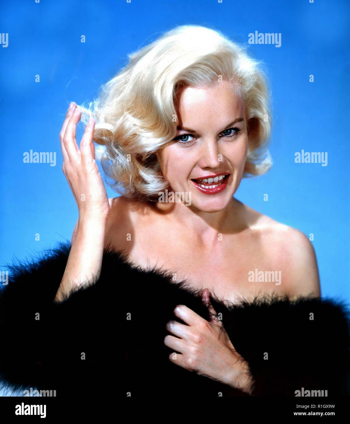 Carroll Baker (born May 28, 1931) is a retired American actress of film, stage, and television. Throughout the 1950s and 1960s, Baker's range of roles from naive ingénues to brash and flamboyant women established her as both a serious dramatic actress and a pin-up. After studying under Lee Strasberg at the Actors Studio, Baker began performing on Broadway in 1954, where she was recruited by director Elia Kazan to play the lead in the film of Tennessee Williams's Baby Doll (1956). Her role in the film as a sexually repressed Southern bride earned her BAFTA and Academy Award nominations for Best - Stock Image