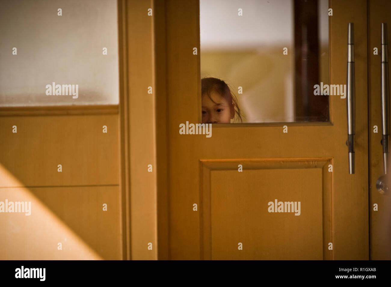 Girl peeking through the doors of a gym. - Stock Image